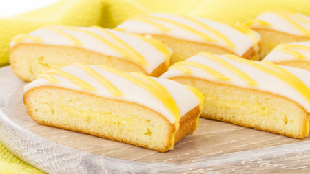 drizzle: Lemon Drizzle Cake - Slices of lemon cake topped with icing.
