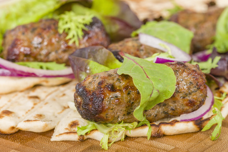 minted: Lamb Kebabs in Flatbread - Minted minced lamb kebabs in flatbreads with salad and sauces. Stock Photo