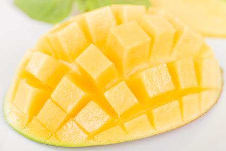 mango: Mango - Hedgehog style cut ripe mango half on a white background.