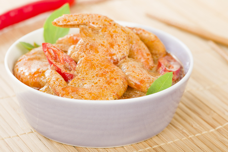 exotic food: Thai Prawn Curry - King prawns in red curry sauce and coconut milk in a lilac bowl. Stock Photo