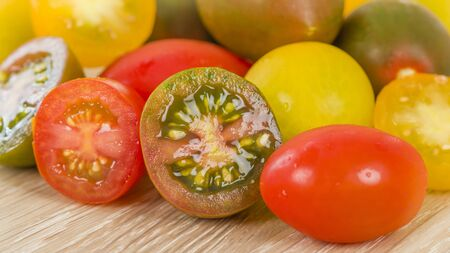 Tomatoes - Variety of different colour tomatoes on a wooden board.