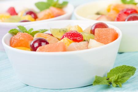 Fruit Salad - Bowls of fresh fruit salad on a blue background.