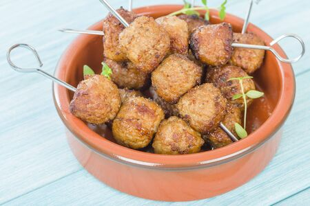BBQ Meatballs - Meatballs on metal skewers on a blue background.