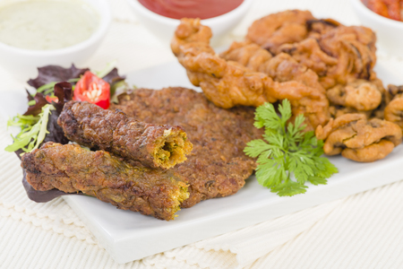 South Asian Starters - Selection of seekh and shami kebabs, mushroom and chicken pakoras and onion bhajjis. Served with salad, mint raita, lime pickled and chilli sauce.