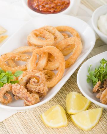 Calamari - Deep-fried squid rings served with garlic mayo and chili sauce. Reklamní fotografie