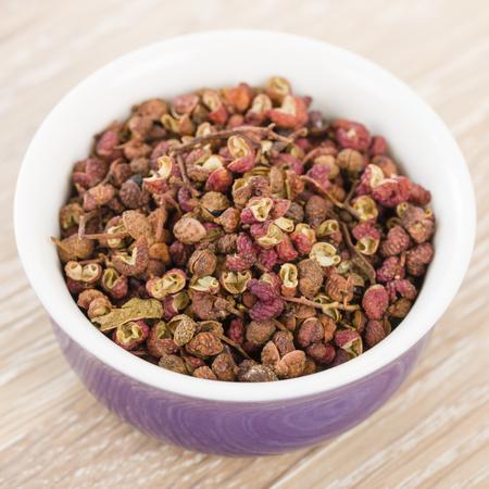 Szechuan Pepper - Szechuan peppercorns in a purple bowl.