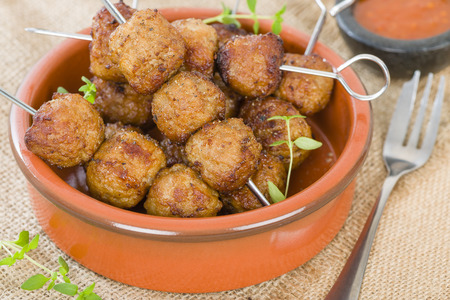 BBQ Meatballs - Meatballs on metal skewers served with chilli dip. Stock Photo