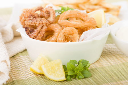 Calamari - Deep-fried squid rings served with lemon on a white background.
