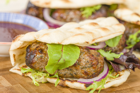 Lamb Kebabs in Flatbread - Minted minced lamb kebabs in flatbreads with salad and sauces. Stock Photo