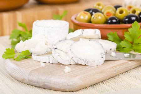 Aceitunas queso de cabra - molde de queso de leche de grasa completa madurado de cabra suave sirvió con las aceitunas mixtas. Foto de archivo