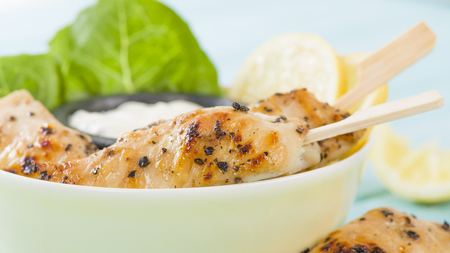 Chicken Satay - Char-grilled spicy mini chicken fillet skewers served with lemon and aioli dip inside a bowl. Stock Photo