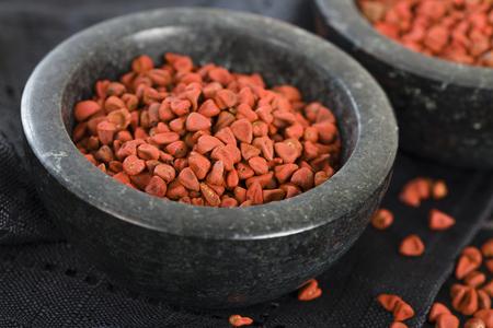 jamaican: Annatto Seeds - Annatto achiote seeds in a black bowl.