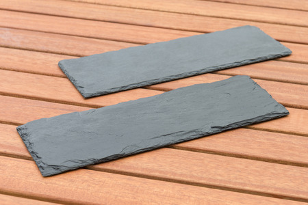 platters: Empty Slate - Black serving platters on a wooden table outdoors.