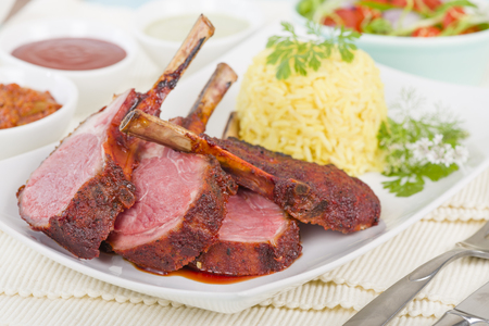 Lamb Cutlets - Spicy roasted lamb cutlets served saffron rice and dips. Stock Photo