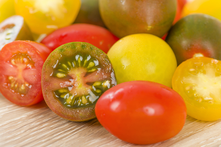 color: Tomatoes - Variety of different colour tomatoes on a wooden board.