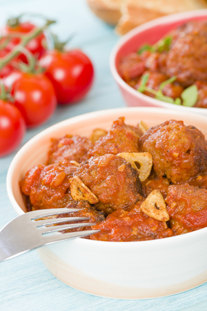slivers: Albondigas Guisadas - Meatballs in tomato sauce with garlic slivers and thyme leaves.
