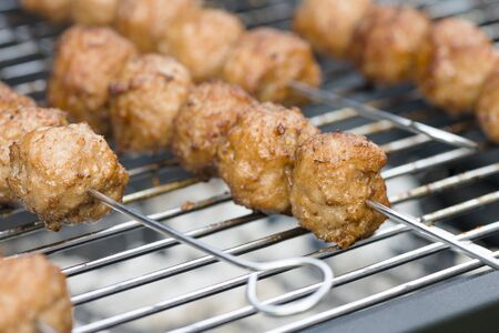 BBQ Meatballs - Meatballs on metal skewers being grilled on a barbecue. Stock Photo