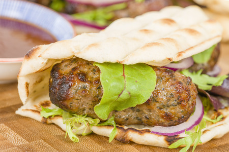 Lamb Kebabs in Flatbread - Minted minced lamb kebabs in flatbreads with salad and sauces. Reklamní fotografie