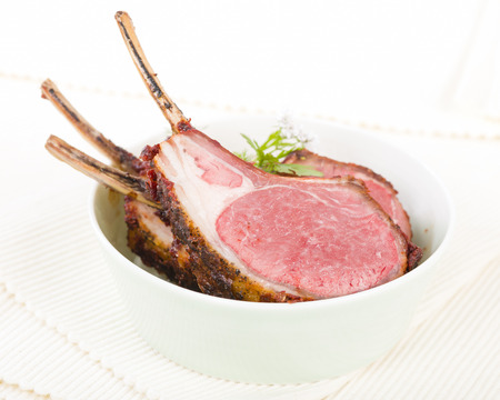 backcground: Lamb Cutlets - Spicy roasted lamb cutlets in a bowl.