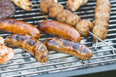 chargrill: Mixed Grill BBQ - Burgers, kebabs, satay and sausages on a barbecue.