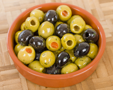 extra virgin olive oil: Olives - Bowl of a variety of black and green olives with herbs and olive oil.