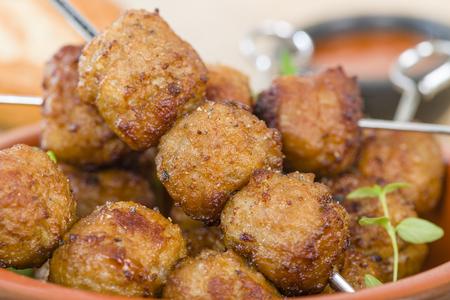 nem: BBQ Meatballs - Meatballs on metal skewers served with chilli dip. Stock Photo