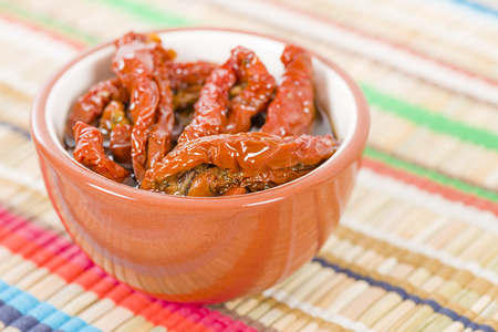 sundried: Sun-dried Tomatoes - Bowl of sun-dried tomatoes in olive oil on a colourful background.