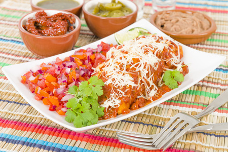 Chicken  Chorizo Enchiladas - Mexican soft tortilla filled with chorizo and chicken cooked in spicy tomato sauce. Served with salsa, refried beans and jalapenos.
