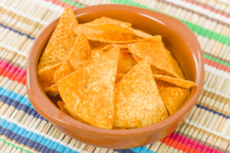 totopos: Totopos - Mexican tortilla chips on a colourful background. Stock Photo