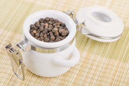 peppercorns: Peppercorns - Black peppercorns in a white jar.