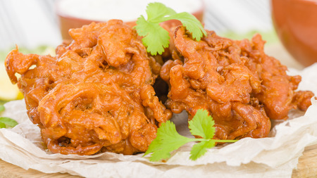 onion bhaji: Onion Bhajis - South Asian fritters served with lime chutney and mint raita. Stock Photo
