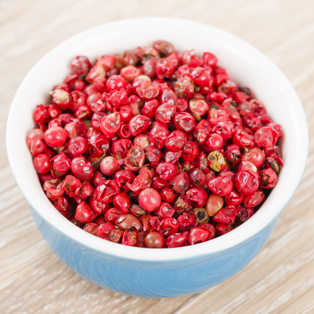 peppertree: Pink Peppercorns - Bowl with dried pink peppercorns on a wooden background.