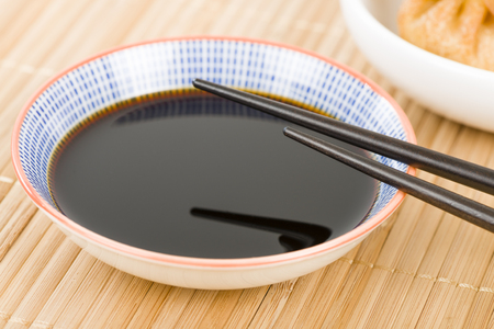 hoisin: Soy Sauce - Close up of chopsticks resting on a small bowl of asian dipping sauce.