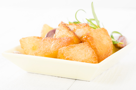 roast potatoes: Roast Potatoes - White potatoes roasted with garlic and rosemary in goose fat on a white background. Stock Photo