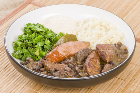 rice plate: Feijoada - Brazilian beef, sausage, pork and black bean stew served with manioc flour, kale and white rice. Stock Photo