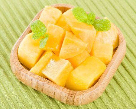 mango: Mango - Kawałki mango na placu bambusowe miseczki na zielonym tle.