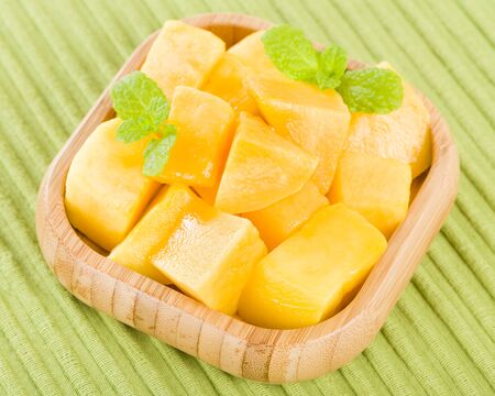 mango: Mango - Pieces of mango in a square bamboo bowl on a green background. Stock Photo