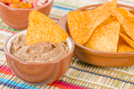 Tortilla Chips  Dips - Mexican totopos with refried beans and salsa. Reklamní fotografie - 49521785