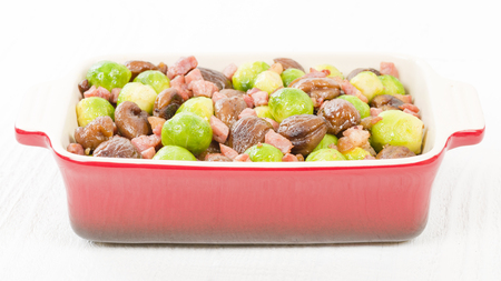 Sprouts, Chestnuts  Bacon - Brussels sprouts cooked with lardons and chestnuts on a white background. Traditional Christmas side dish.