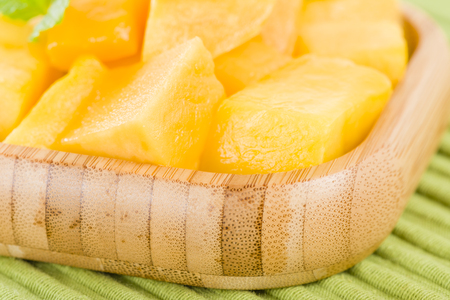 Mango hedgehog style cut ripe mango half on a white background mango pieces of mango in a square bamboo bowl on a green background photo ccuart Choice Image