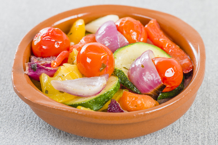 cazuela: Mediterranean Roasted Vegetables - Pepper, tomatoes, red onions and courgette roasted with olive oil and served in a cazuela. Stock Photo