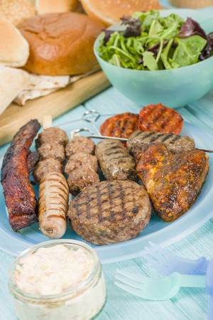piri: BBQ - Assorted barbequed meat and bread on a blue background. Served with coleslaw, yoghurt and cucumber dip and chili sauce. Outdoors summer meal! Stock Photo