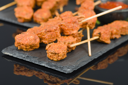 cooked pepper ball: Spicy Chicken Satay - Marinated chicken meatball skewers served with chilli sauce and lemon wedges on a slate with reflections.