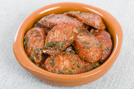 cazuela: Chorizo  Herbs - Fried chorizo with chopped herbs served in a cazuela.