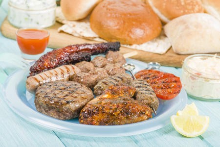 seekh: BBQ - Assorted barbequed meat and bread on a blue background. Served with coleslaw, yoghurt and cucumber dip and chili sauce. Outdoors summer meal! Stock Photo