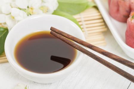 hoisin sauce: Dumpling Sauce - Close up of chopsticks resting on a small white bowl of asian dipping sauce. Stock Photo