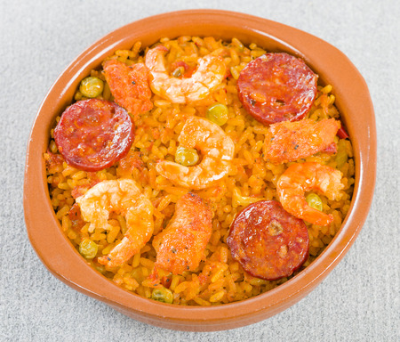 cazuela: Mixed Paella - Individual portion of mixed paella with chicken, chorizo and prawns in a cazuela. Stock Photo