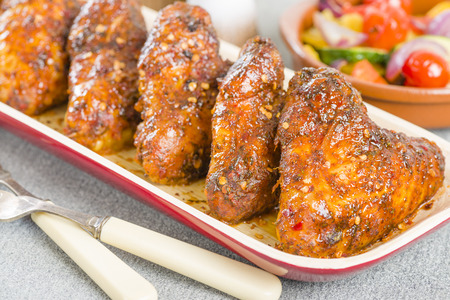 piri: Spicy Hot Chicken Wings - Platter of chicken wings coated in hot sauce. Stock Photo