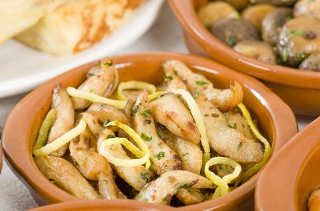 limon: Pollo al limon con ajo Chicken with lemon and garlic. Traditional Spanish tapas dish. Stock Photo