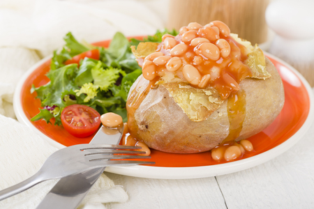 Jacket Potato - Baked potato topped with cheese and baked beans served with salad. Reklamní fotografie